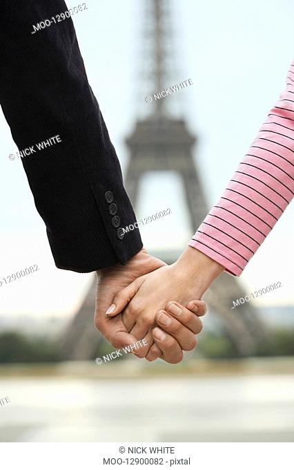 France Paris Couple holding hands in front of Eiffel Tower close up of hands