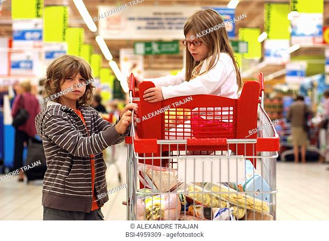 Models. Children of 4 and 8 years old in a supermarket