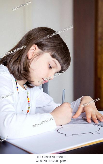 Portrait of little girl painting with wax crayon