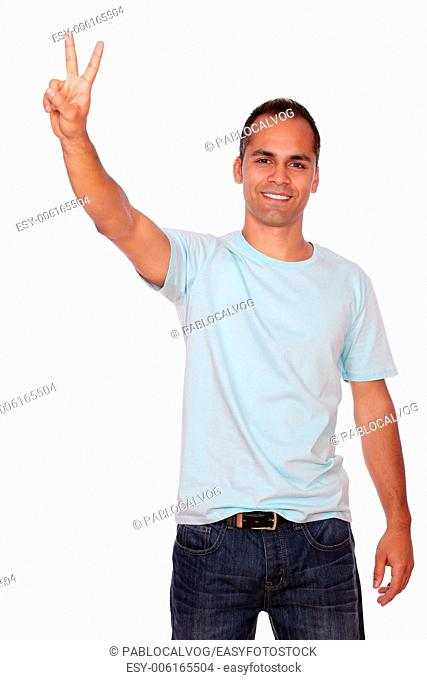 Portrait of a smiling young man showing you victory sign on white background
