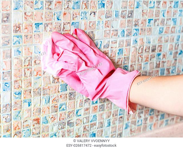 House cleaning - hand washes ceramic tiles on kitchen wall