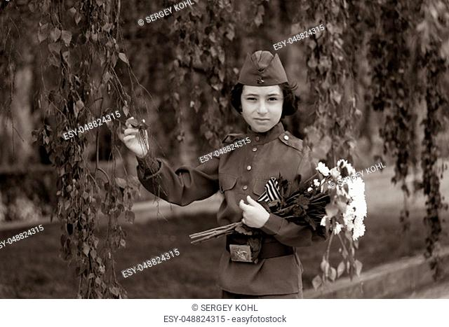 Portrait of a boy with flowers, in the uniform of a soldier of the Red Army during the Second World War. Stylization. Sepia