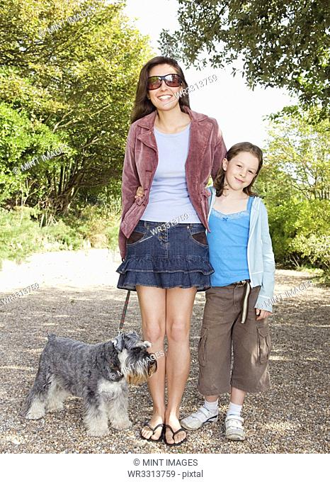 Caucasian mother and daughter walking dog on path