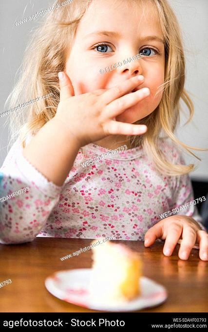 Girl eating a piece of birthday cake