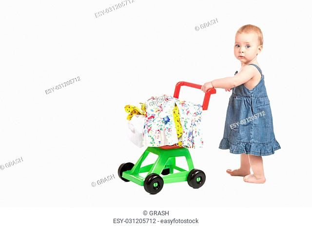 Little girl in denim dress with a trolley full of clothes isolated on white background