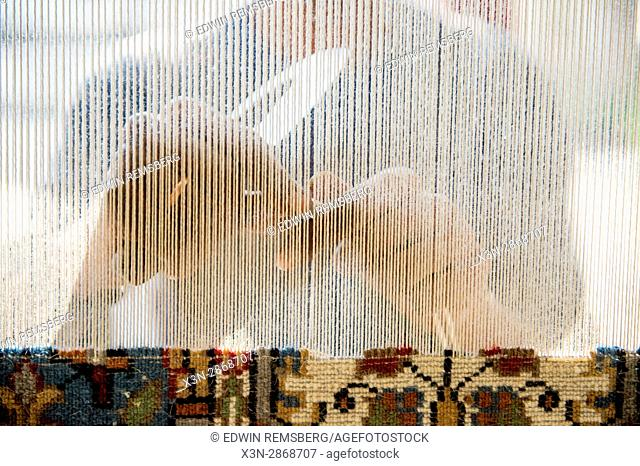 Close up view of hands weaving an oriental rug at a shop in Jaipur, India