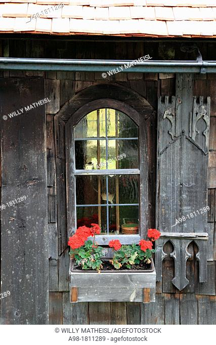 Geranium flowers decorating a window of a wooden chapel at the Farmhouse Museum Lindberg, Bavarian Forest, Bavaria, Germany, Europe