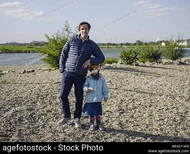 Father with daughter standing on land against Rhine river during sunny day