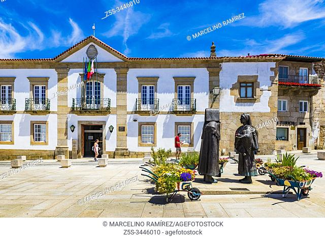 Plaza Joao III, two statues made in bronze with the typical regional costumes of the region of Tras os Montes, in the background the town hall, Miranda do Douro