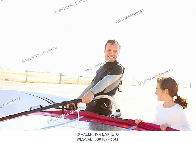 Smiling man with daughter at the coast with surfboard