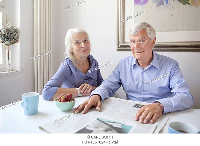Portrait of happy senior couple sitting with newspaper at table