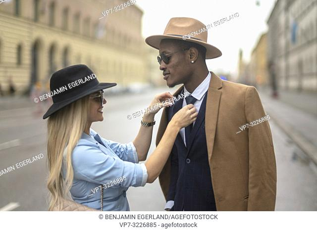 Woman fixing tie of man, Munich, Germany