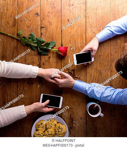Young couple holding hands and their smartphones