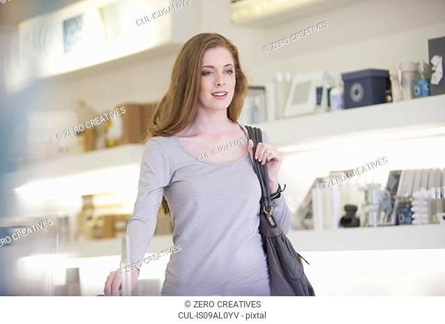 Woman walking past products on display shelves