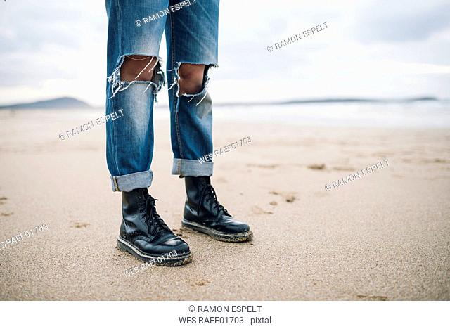 Woman wearing boots and torn jeans on the beach, partial view