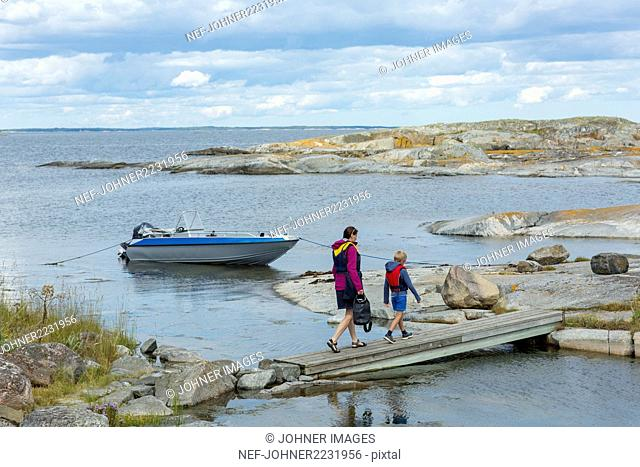 Mother with son walking at sea