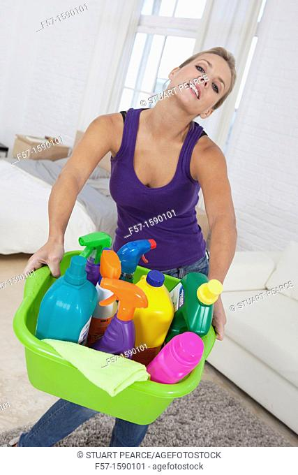 Young woman holding cleaning products
