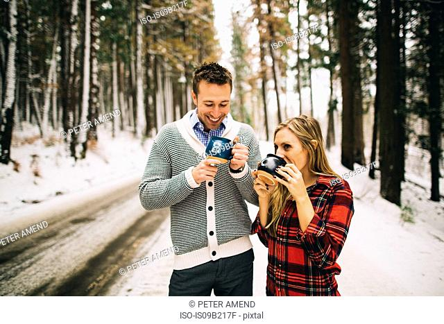 Couple in snow-covered forest drinking hot beverage from mugs