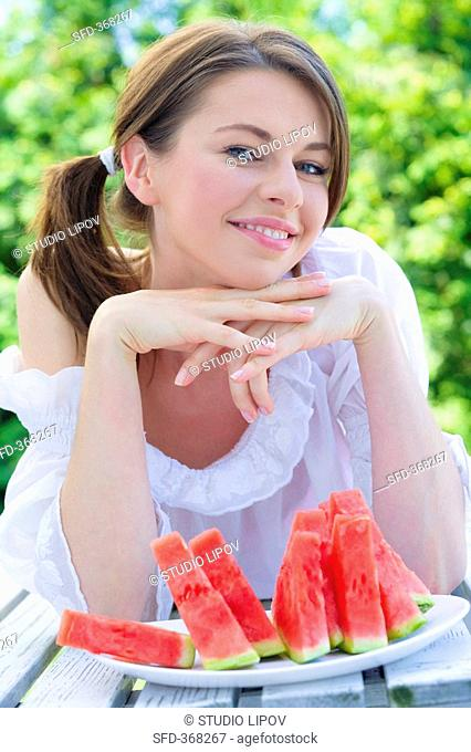 Young woman sitting at table with watermelon