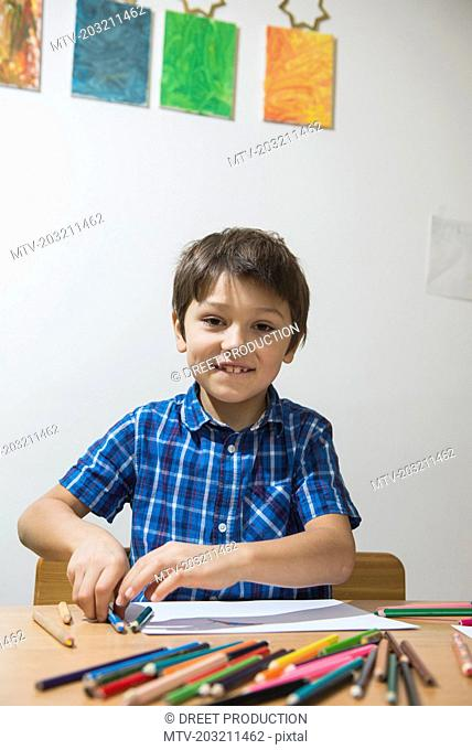 Boy enjoying with coloured pencils while looking at camera, Munich, Germany