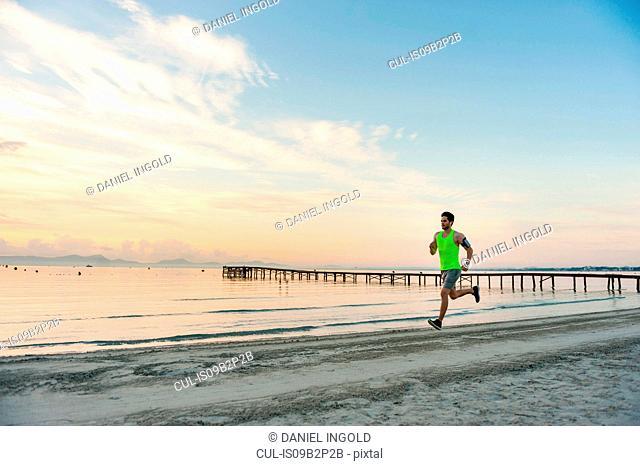 Man jogging on beach, Mallorca, Spain