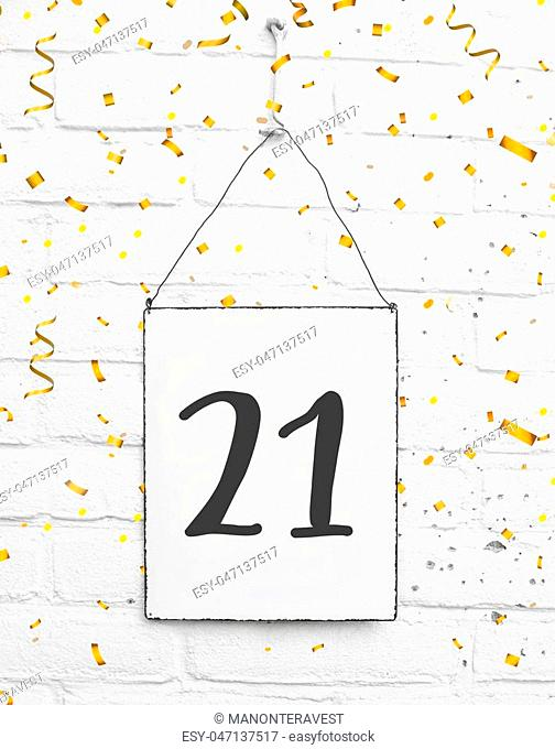 21 years old birthday party card text with golden confetti, number twenty-one, metal plate white brick background