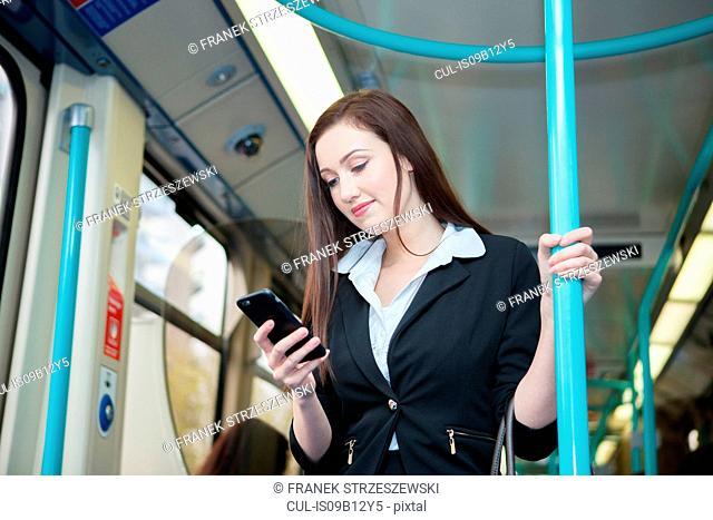 Businesswoman using cellphone in Docklands Light Railway train, London