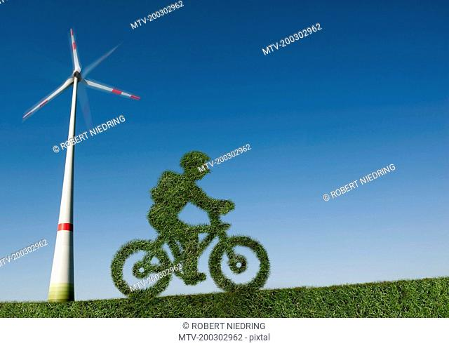 Eco friendly green bicycle in a windfarm, Bavaria, Germany