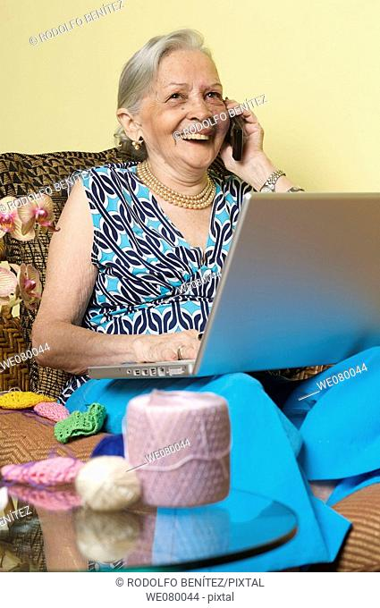 Senior lady speaking on a cell phone using a laptop computer