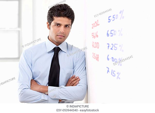 Portrait of executive standing next to white board