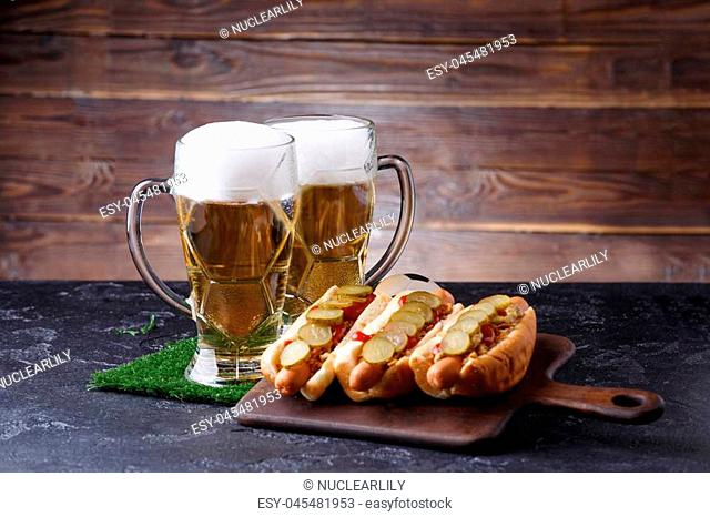 Photo of two glasses of beer, hot dogs, soccer ball on wooden plate on table