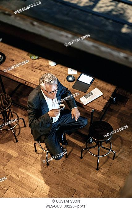 Senior businessman sitting cafe, drinking coffee