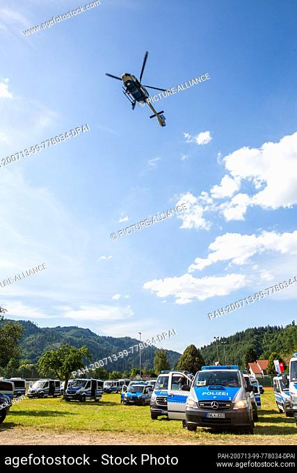 13 July 2020, Baden-Wuerttemberg, Oppenau: A police helicopter flies over a sports field near the community of Oppenau, where police vehicles are parked and...