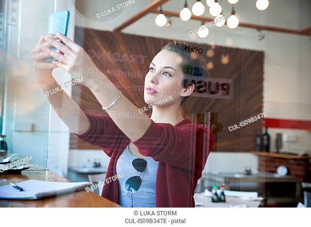 Young woman sitting in cafe, taking selfie, using smartphone