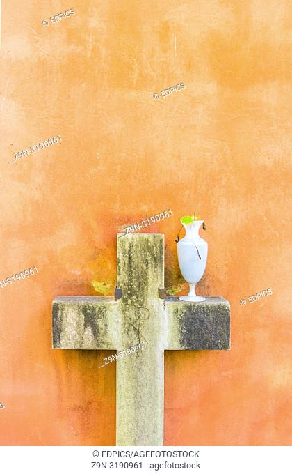 historic stone cross and glass vase against pastel colored background, rome, lazio, italy