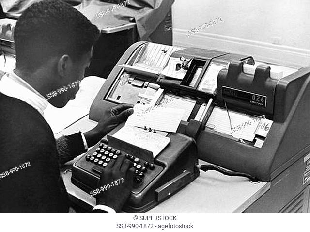 High school student learning to operate a keypunch machine