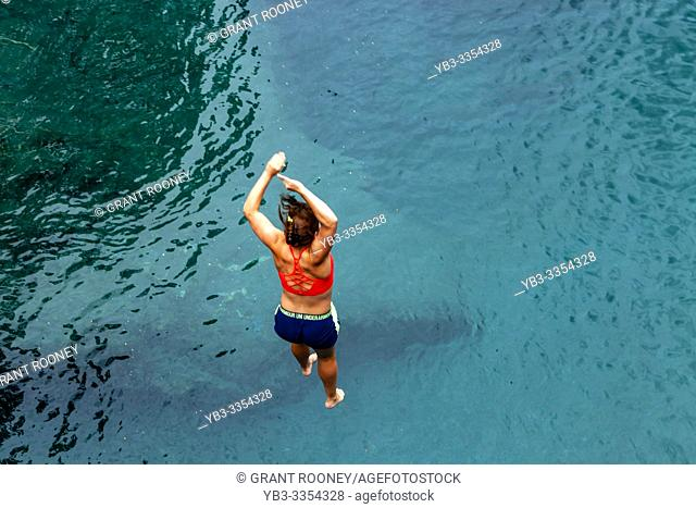 A Young Woman Jumps Into The Blue Pools (near Makarora), Mt Aspiring National Park, South Island, New Zealand