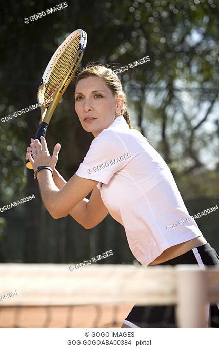 Female tennis player swinging