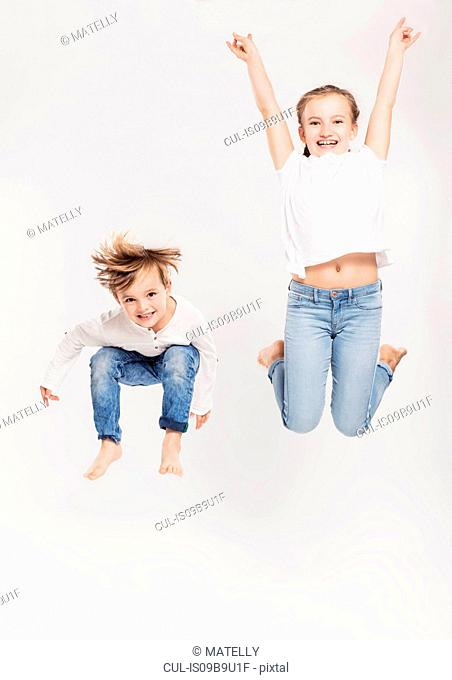 Portrait of brother and sister leaping in air