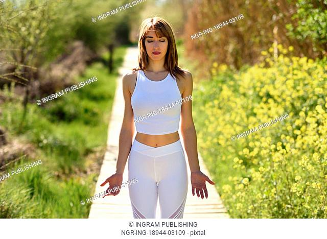 Young woman doing yoga in nature. Female wearing white sport clothes on a wooden road