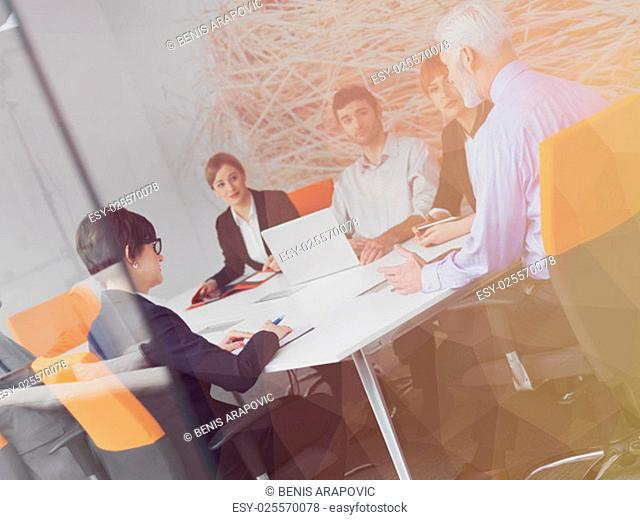 Double exposure with low poly design. Business people group on meeting at modern bright office indoors. Senior businessman as leader in discussion