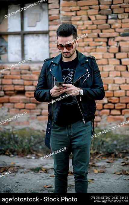 Guy with sunglasses standing on the street and using mobile phone