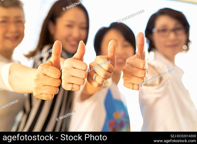 Four women showing thumbs up sign
