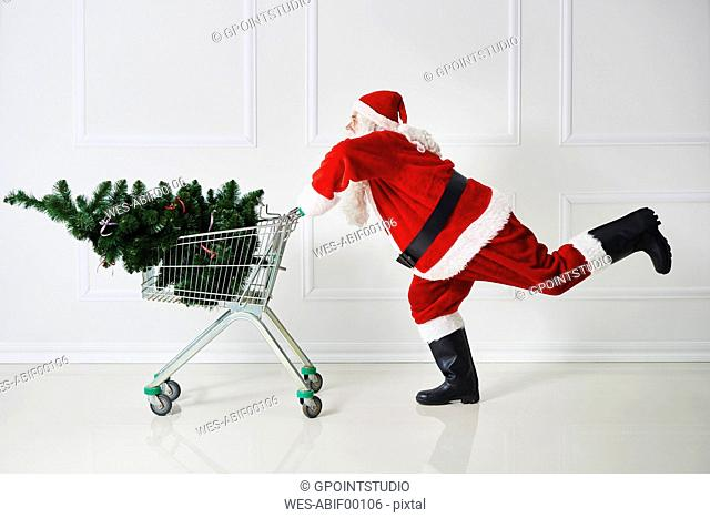 Santa Claus transporting Christmas tree in a shopping cart