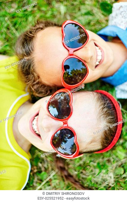 Friendly girls in sunglasses relaxing on grass