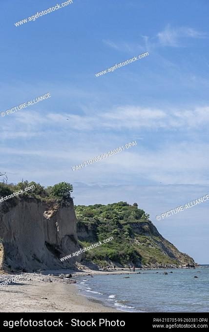26 June 2021, Mecklenburg-Western Pomerania, Hiddensee: Few tourists walk along the steep coast in the north of the island of Hiddensee