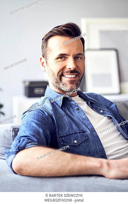 Portrait of smiling man sitting on sofa
