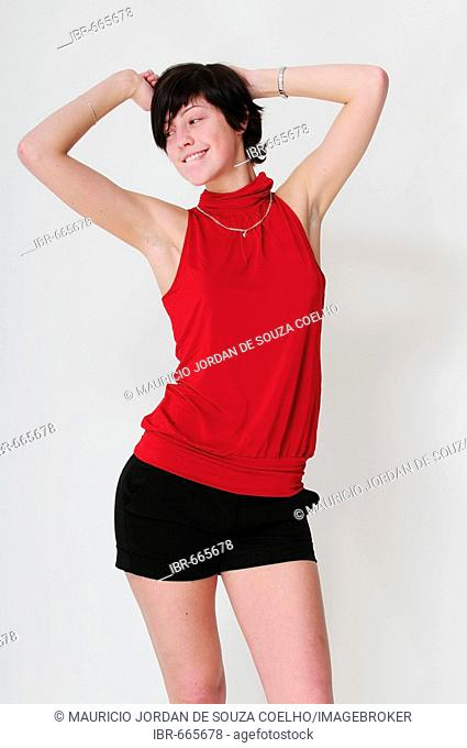 Black-haired woman dancing flirtatiously in front of a white background