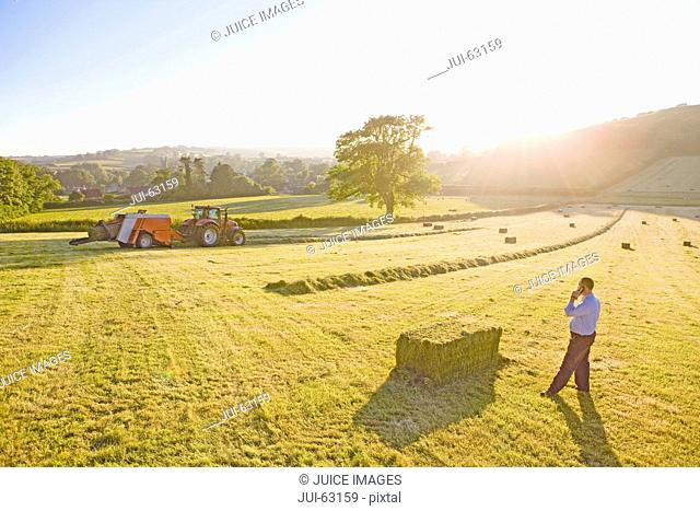 Farmer using mobile phone watching tractor baling hay in field