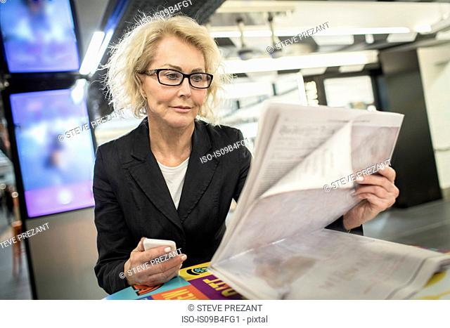 Mature businesswoman reading newspaper in shopping mall cafe